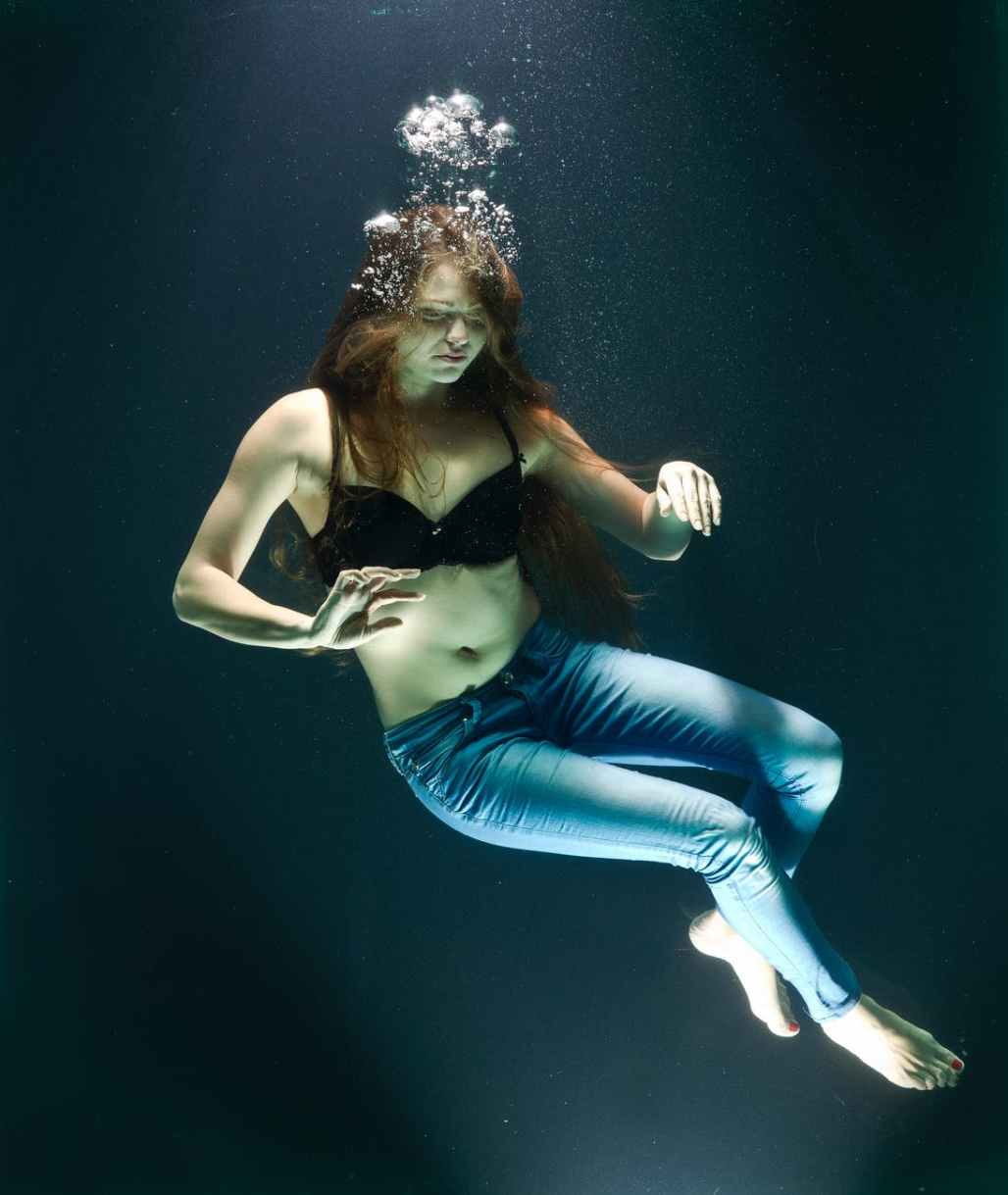 woman wearing black brassiere sinking on the body of water photography